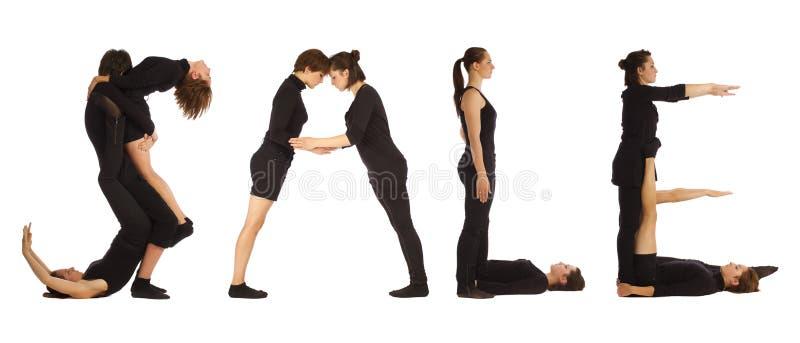 Personnes habillées par noir formant le mot de VENTE photos stock