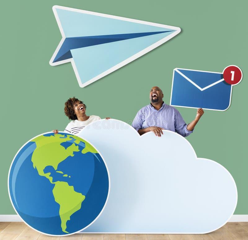 Personnes heureuses avec des icônes de nuage et de technologie image libre de droits