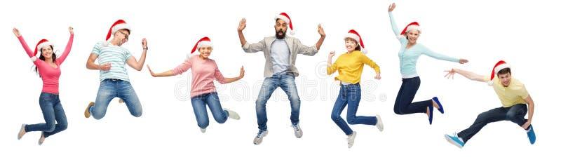 Personnes heureuses dans des chapeaux de Santa sautant en air image libre de droits