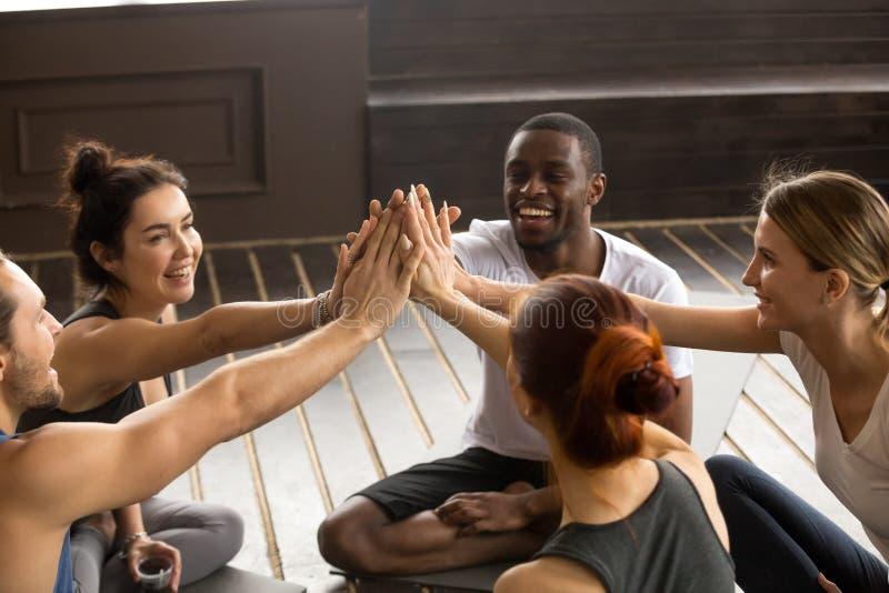 Personnes heureuses sportives convenables donnant la haute cinq à la formation de groupe images libres de droits