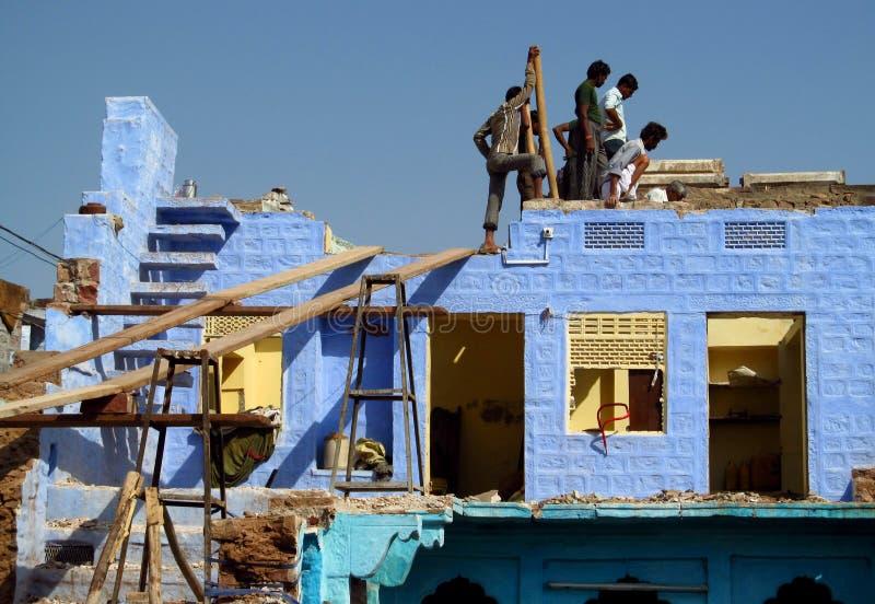 Personnes indoues construisant une maison bleue photographie stock libre de droits