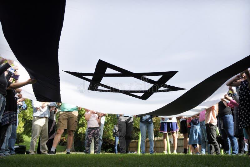 Personnes juives israéliennes tenant un drapeau national géant de l'Israël photos libres de droits
