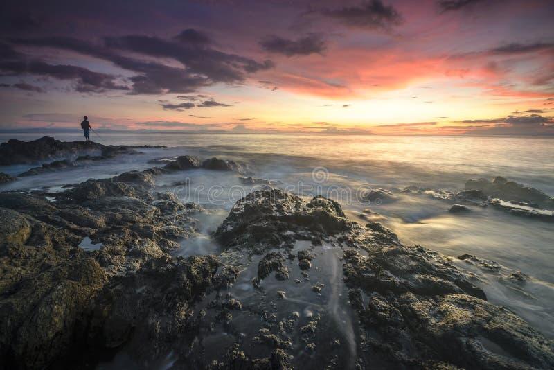 Personnes locales en silhouette appréciant la pêche pendant le coucher du soleil à l'île de Lombok, Indonésie photographie stock