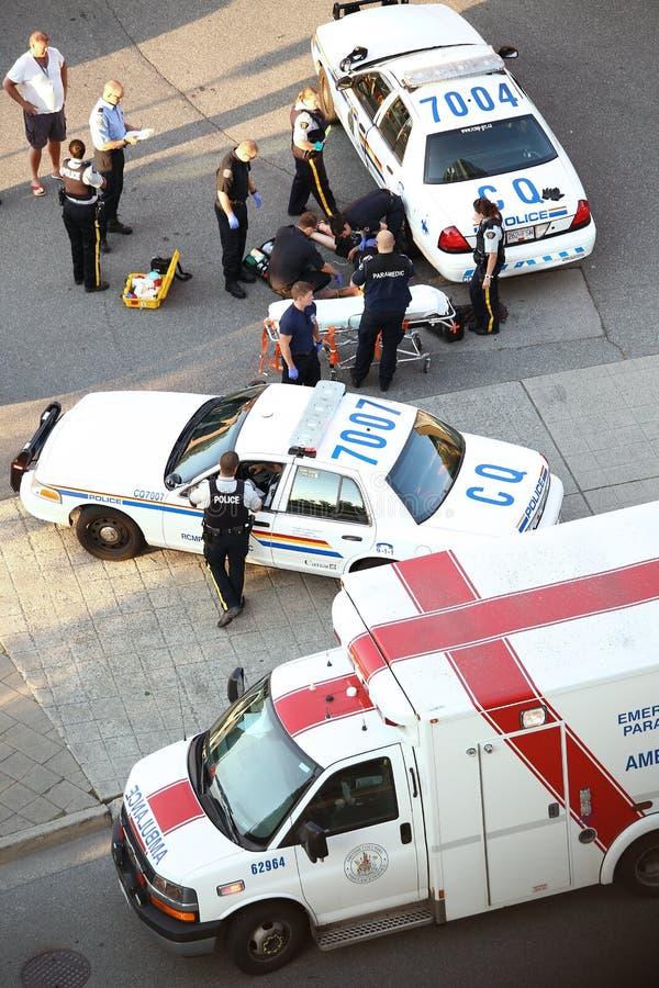 Personnes médicales et homme de aide de crise cardiaque de police photo stock