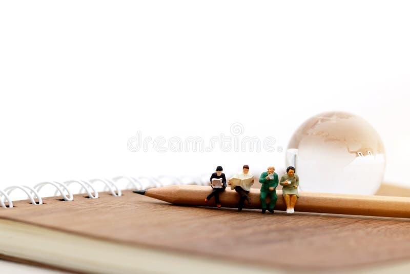 Personnes miniatures : Équipe d'affaires s'asseyant sur le crayon et le livre photo libre de droits