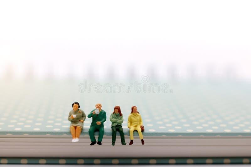 Personnes miniatures : équipe d'affaires s'asseyant sur le livre avec la pause-café photo libre de droits