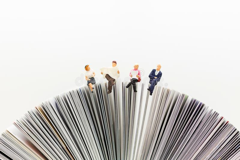Personnes miniatures, équipe d'affaires s'asseyant sur le livre, lisant le papier d'actualités, employant comme affaires de fond, photographie stock libre de droits