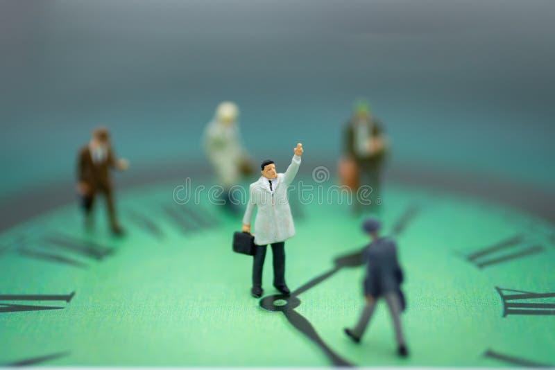 Personnes miniatures : Équipe d'homme d'affaires avec l'horloge L'utilisation d'image prennent du temps de bénéficier images stock