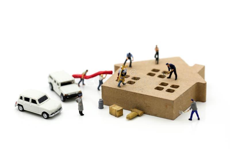 Personnes miniatures : équipe de travailleur avec la maison et la voiture, la réparation ou le hom photographie stock libre de droits