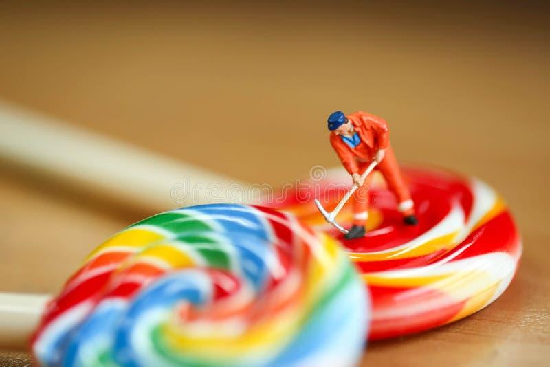 Personnes miniatures : équipez le travailleur avec coloré des sucreries et flânez photographie stock