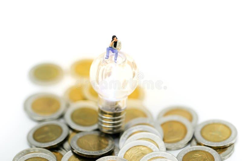 Personnes miniatures : équipez se reposer avec des pièces de monnaie et l'idée de lampe, affaires photographie stock