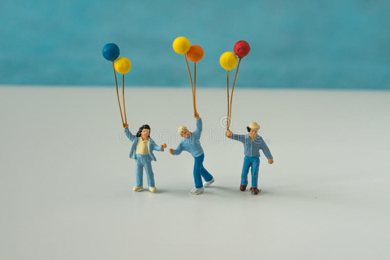 Personnes miniatures avec la famille tenant le ballon avec le CCB bleu de couleur photos libres de droits