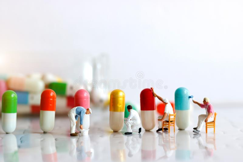 Personnes miniatures : Brosse d'équipe de travailleurs peignant la capsule médicinale image stock
