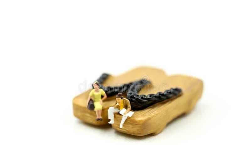 Personnes miniatures : personnes de couples s'asseyant sur la chaussure en bois japonaise photo stock