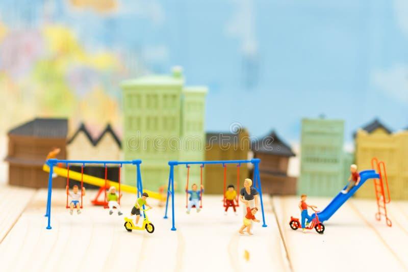 Personnes miniatures : Enfantez le jeu avec le fils et beaucoup d'enfants au terrain de jeu Utilisation d'image pour le jour inte photos libres de droits