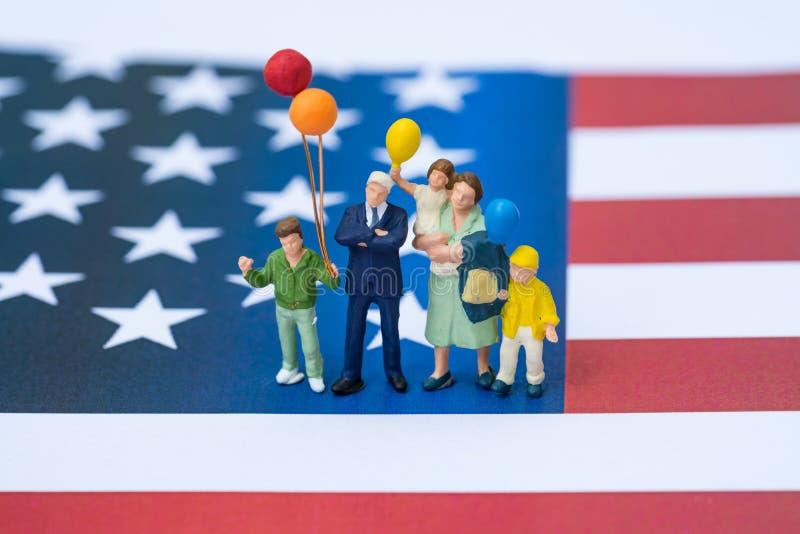 Personnes miniatures, famille américaine heureuse tenant le ballon avec Uni photos stock