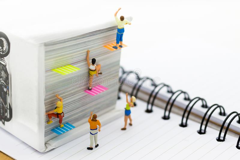 Personnes miniatures : Grimpeur s'élevant sur le livre Utilisation d'image pour apprendre, concept d'éducation photo stock
