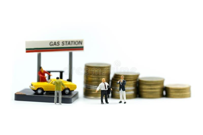 Personnes miniatures : Homme d'affaires On Gas Station avec des pièces de monnaie, affaires images libres de droits