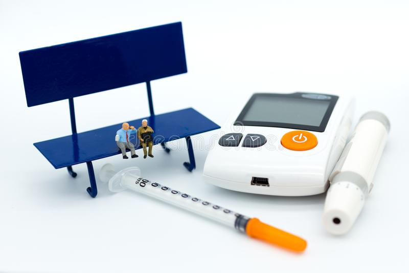 Personnes miniatures : Homme d'affaires s'asseyant sur la chaise avec le mètre de glucose, seringue Utilisation d'image pour le c photo stock