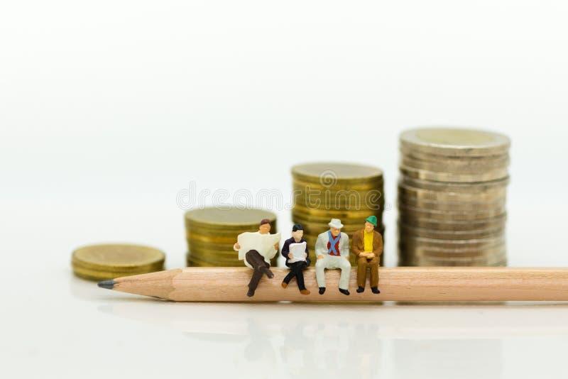 Personnes miniatures : Homme d'affaires s'asseyant sur le crayon et lisant le journal, pile de pièces de monnaie de fond Utilisat image stock