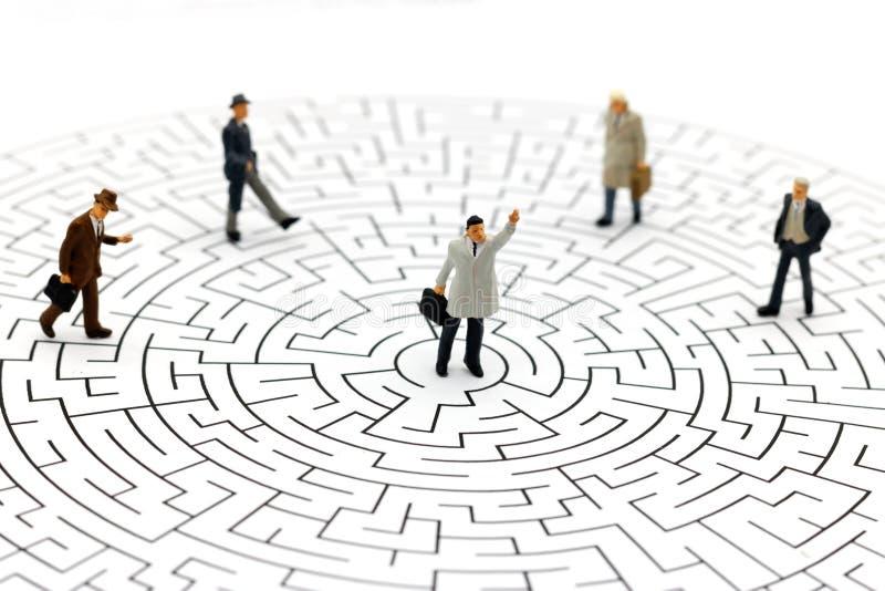 Personnes miniatures : Homme d'affaires se tenant au centre du labyrinthe photo stock