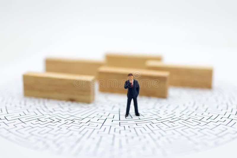 Personnes miniatures : Homme d'affaires se tenant avec un labyrinthe au fond Utilisation d'image pour la solution de découverte,  image stock