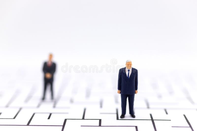 Personnes miniatures : Homme d'affaires se tenant avec un labyrinthe au fond Utilisation d'image pour la solution de découverte,  image libre de droits