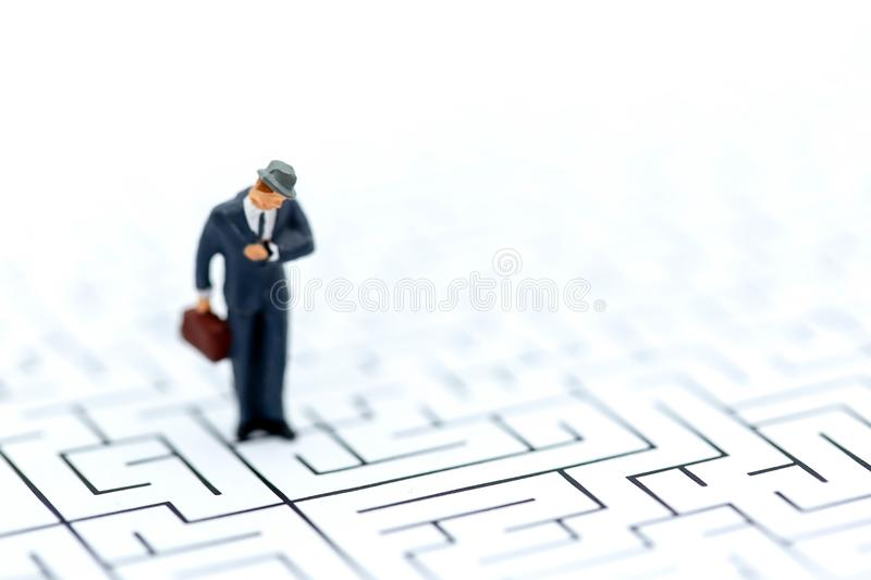 Personnes miniatures : homme d'affaires se tenant sur le labyrinthe, concepts de fi photo stock