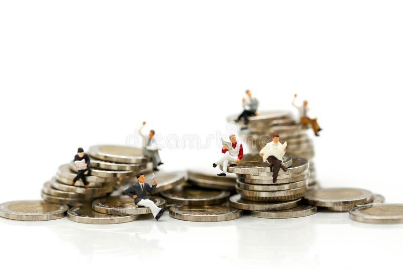 Personnes miniatures : hommes d'affaires s'asseyant sur des pièces de monnaie et lisant des actualités images libres de droits