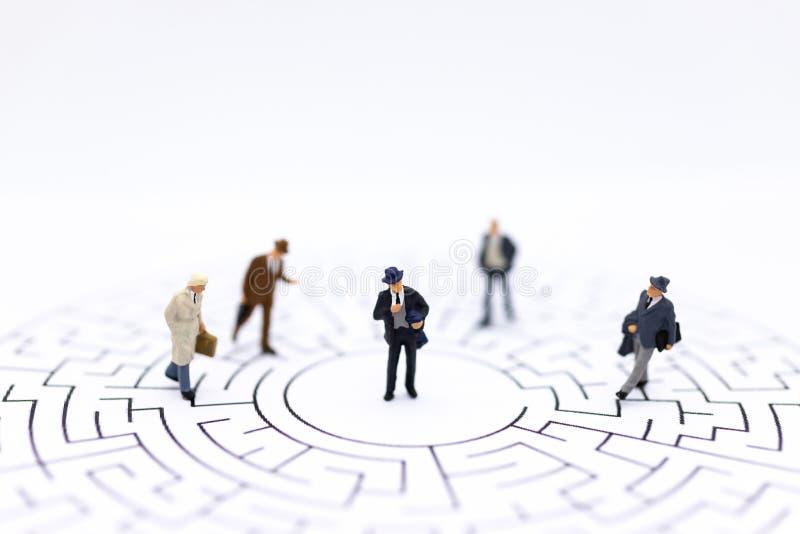 Personnes miniatures : Hommes d'affaires se tenant sur la carte de labyrinthe et recherchant une solution avec le travail d'équip photo stock