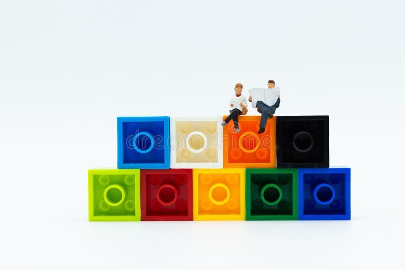Personnes miniatures : journal de lecture d'homme d'affaires sur le bloc coloré Utilisation d'image pour l'éducation de fond, con image stock