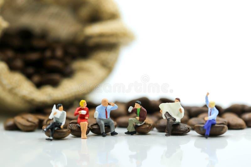 Personnes miniatures : l'équipe d'affaires s'asseyant sur des grains de café, détendent c photos libres de droits