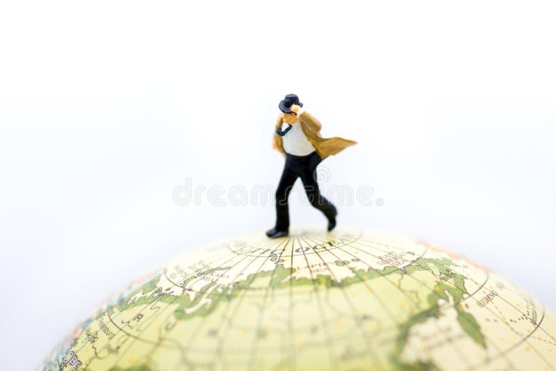 Personnes miniatures : l'homme d'affaires et le lien soufflant en vent se tiennent sur la carte du monde Utilisation d'image pour photographie stock libre de droits