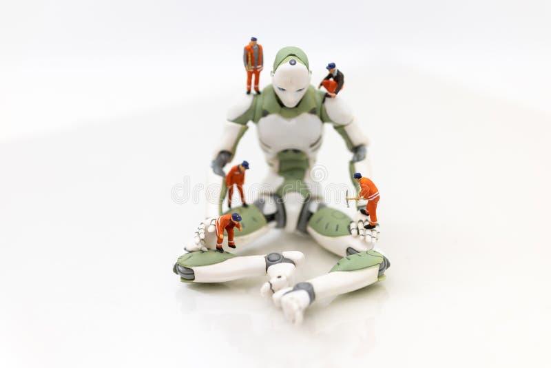 Personnes miniatures : L'ingénierie développe un système de robot d'AI, utilisant le travail au lieu des personnes Utilisation d' images libres de droits