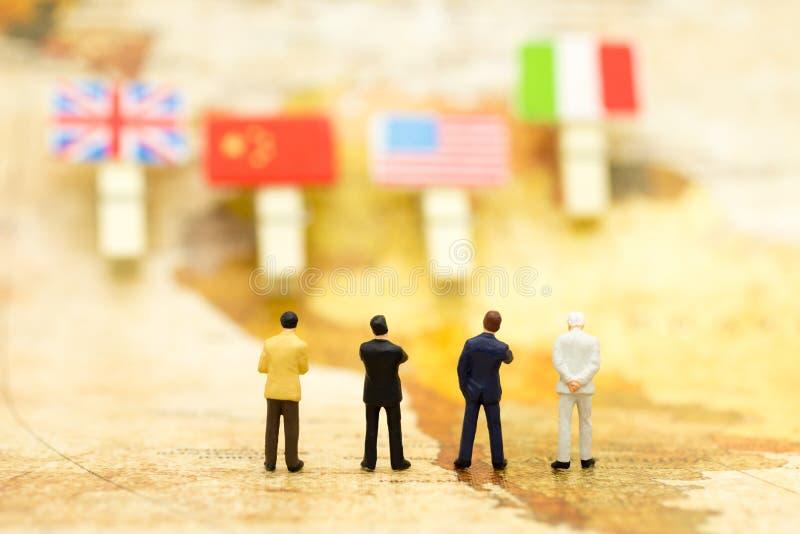 Personnes miniatures : Le support d'homme d'affaires sur la carte et recherchent le pays des affaires Concept d'affaires d'utilis photographie stock libre de droits