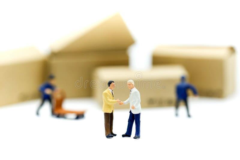 Personnes miniatures : les hommes d'affaires remettent la vérification, se tenant dans l'avant photo stock