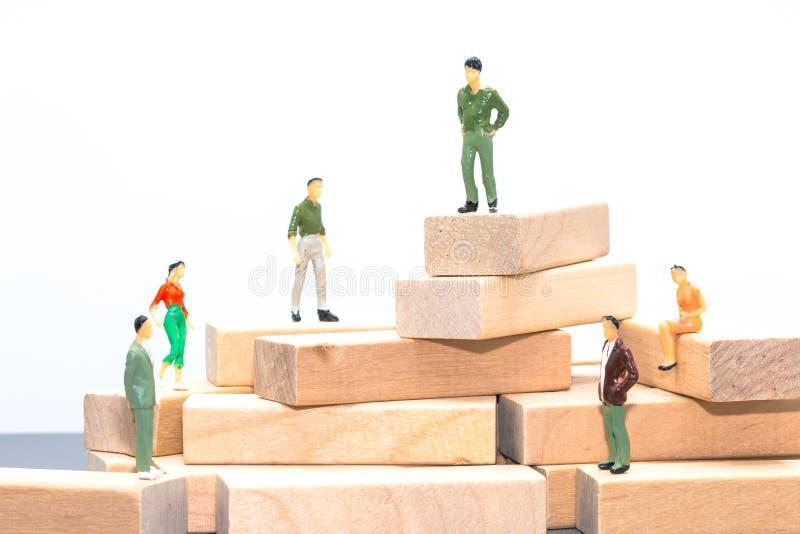 Personnes miniatures : les petits chiffres hommes d'affaires se tiennent et se reposent sur l'OE photos stock