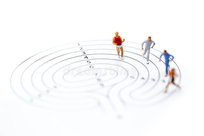 Personnes miniatures : marathoniens sur le labyrinthe, pulsant et fonctionnant photographie stock