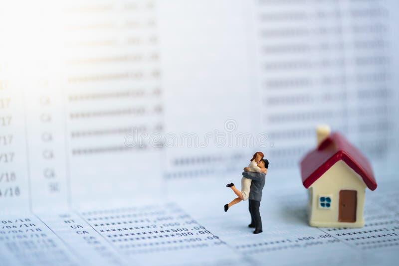 Personnes miniatures : Petits chiffres de couples dans l'amour se tenant sur le carnet de banque r Finances de famille photos libres de droits