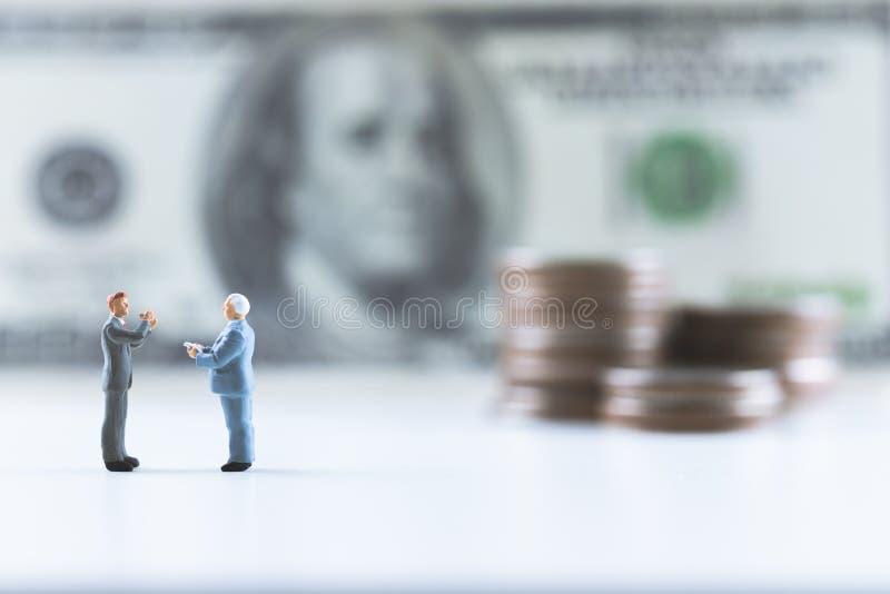 Personnes miniatures, position d'homme d'affaires sur le billet d'un dollar avec la pile de pièce intensifier le fond photo stock