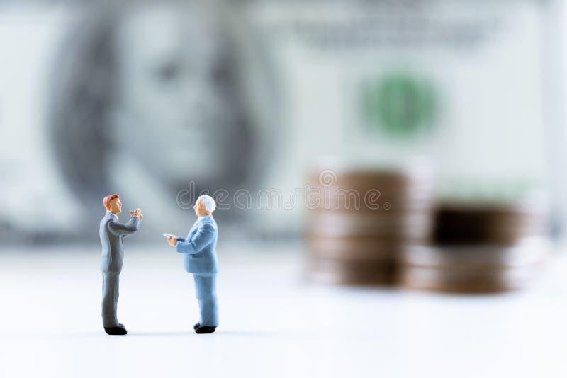 Personnes miniatures, position d'homme d'affaires sur le billet d'un dollar avec la pile de pièce intensifier le fond photo libre de droits