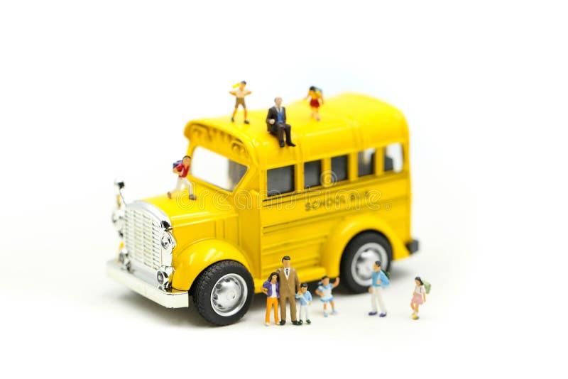 Personnes miniatures : professeur et ?tudiant avec les outils de dessin color?s et stationnaire de l'autobus scolaire, concept d' photo libre de droits