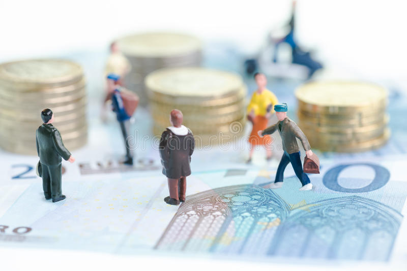 Personnes miniatures sur d'euro billets de banque image stock