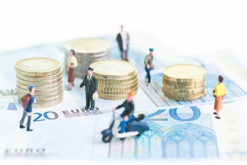 Personnes miniatures sur 20 euro billets de banque et euro pièces de monnaie photo stock