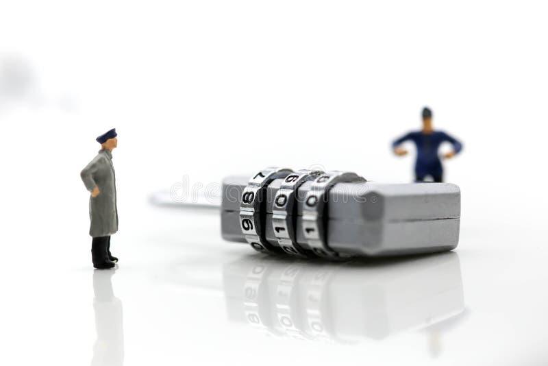 Personnes miniatures : travailleur essayant d'ouvrir une clé machine de sécurité photographie stock