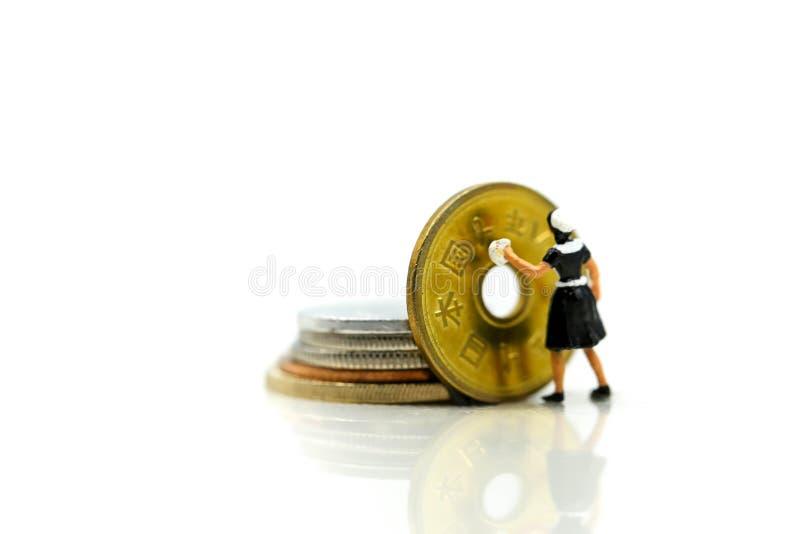 Personnes miniatures : travailleur et domestique nettoyant les pièces de monnaie d'or Business image libre de droits