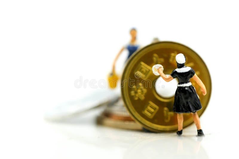 Personnes miniatures : travailleur et domestique nettoyant les pièces de monnaie d'or Business photographie stock libre de droits
