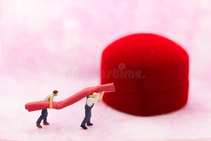 Personnes miniatures : Travailleurs portant les tapis rouges Utilisation d'image pour des mariages photos stock