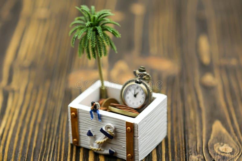 Personnes miniatures : un homme s'asseyant avec le coffre de trésor de l'or images stock