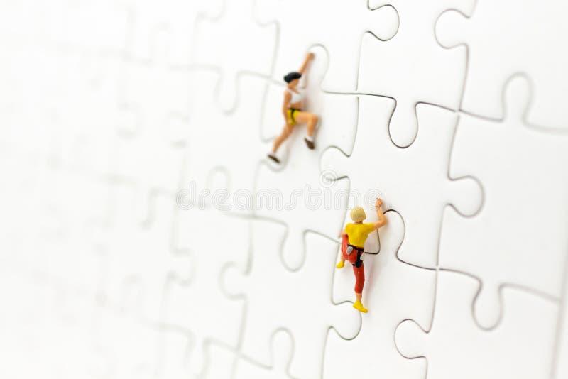 Personnes miniatures : Voyageur, grimpeur sur le conseil denteux Utilisation d'image pour de résoudre des problèmes, trouvant la  photographie stock libre de droits